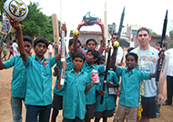 Tommy Marrett standing with Chennai orphans holding the gifts that Tommy gave them