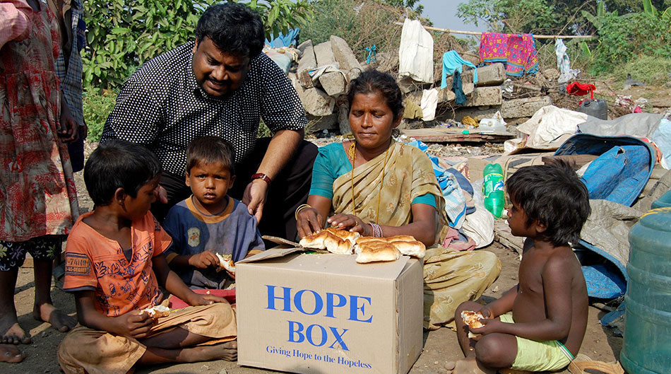 Kingsly with a family that he gave a hope box to
