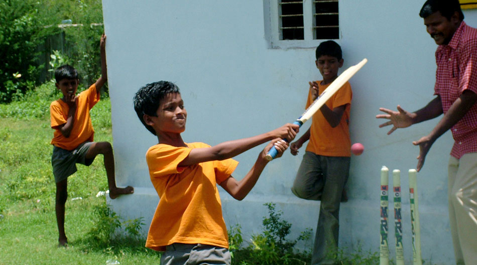 Boys playing cricket with bats, ball and wickets bought by Tommy Marrett